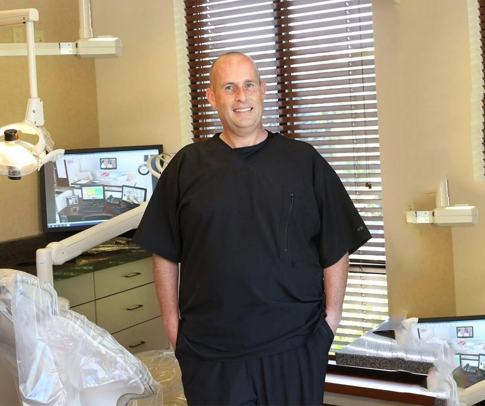 Dr. Lavin leaning on a dental chair in one of our treatment rooms