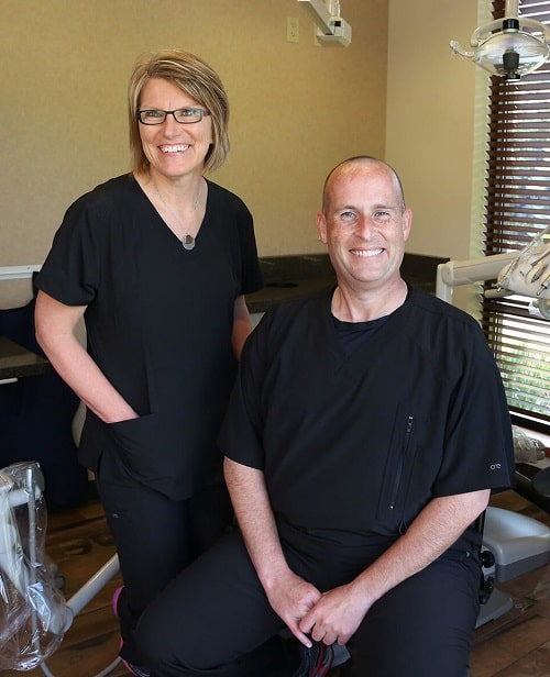 Dr. Lavin sitting next to his dental assistant